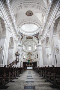 Insidan av en kyrka med vitt innetak.
