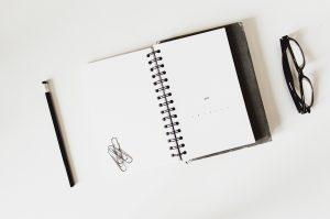 En anteckningsbok och ett par glasögon vid sidan om